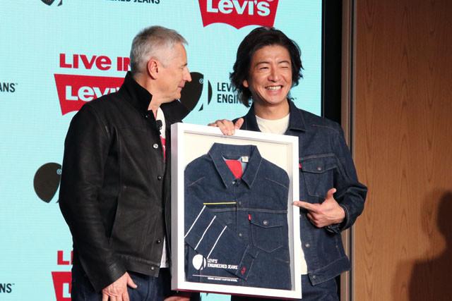 リーバイ・ストラウス ジャパンの代表取締役社長、パスカル・センコフからイニシャル入りカスタムモデルのデニムジャケットを贈呈され、喜ぶ木村