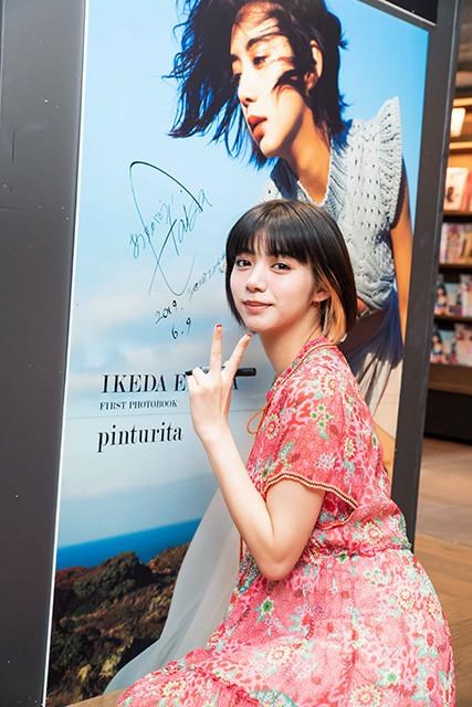 巨大な写真パネルにサインをする池田エライザ