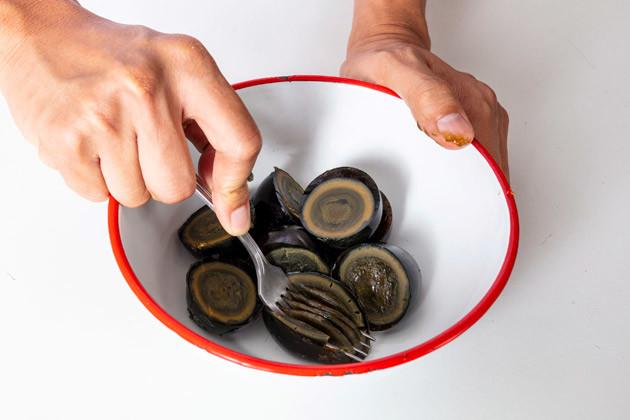 (1)潰す! ピータンの殻をむき、半分に切ってからボウルに移す。続いてフォークやすりこぎなどを用いてピータンを潰そう。ゼリー状の白身部分は弾力があるので力強く押すこと