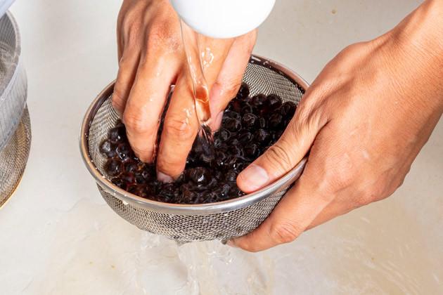 (2)洗う! タピオカそのものにも甘味がついているので、ザルに移して水洗いし、しっかりと甘味を落とす。また、並行してたこ焼き粉に水と卵を混ぜ、たこ焼きのタネを用意しておこう