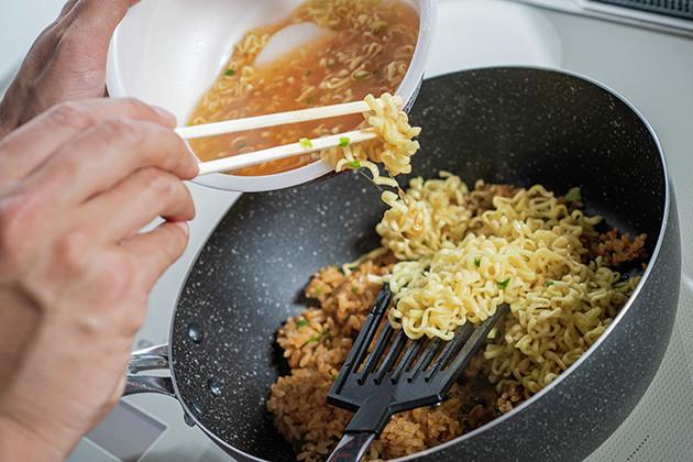 (2)混ぜる! 熱したフライパンに痛快旨辛 麻辣飯を冷凍のまま投入し、軽くほぐしたら辛辛魚の麺も入れてよく混ぜよう。容器に残ったスープも半分くらい流し込み、強火に切り替える