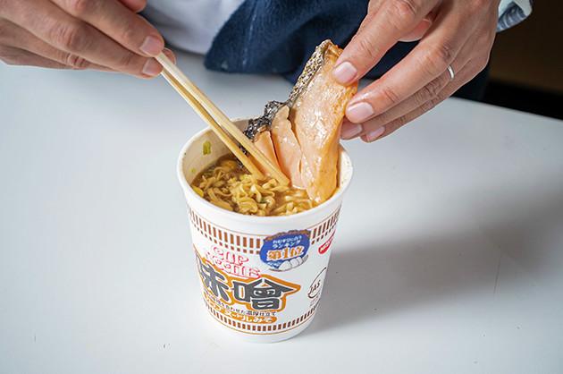 (1)立てる! カップヌードル味噌を作ったら、あらかじめレンチンしておいた銀鮭の塩焼を取り出し、麺に突き刺すようにして立てよう。なんともバカっぽい見た目がたまらない!