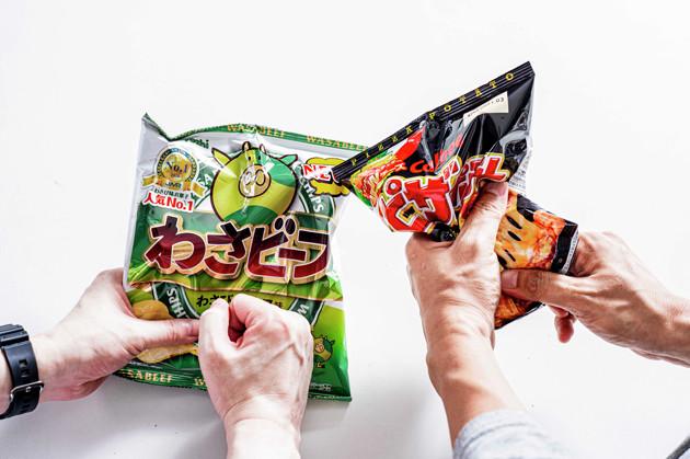 (1)砕く! わさビーフとピザポテトの袋をそれぞれほんの少しだけ開けて空気穴を作り、全体を豪快に揉みほぐしてポテチを砕く。粉々にはしすぎず、1cm角ほどの大きさを目標にしよう