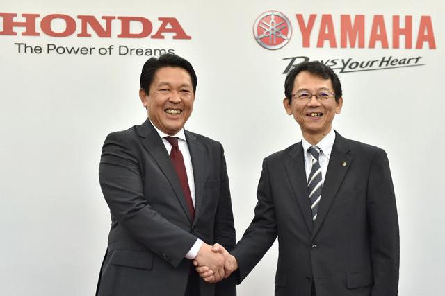 16年、ホンダとヤマハの協業発表の会見で、握手を交わすホンダの青山取締役(左)とヤマハの渡部取締役(右、肩書は当時)