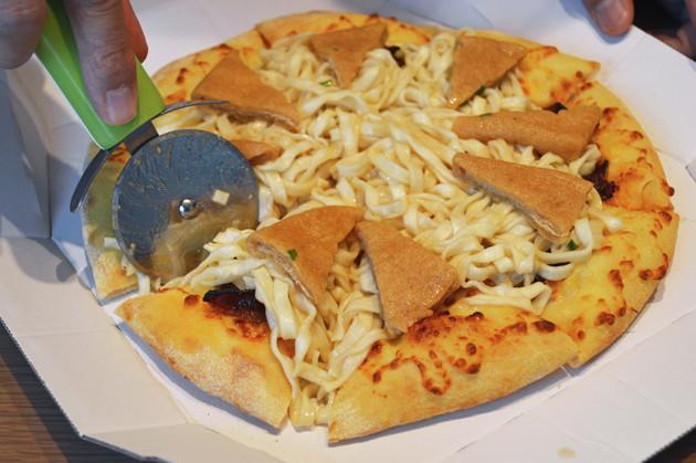 (4)カット! ピザカッターを用意し、ピザがもともとカットされている位置に合わせてどん兵衛の麺もカットする。あとは麺とお揚げを包むようにピザ生地を手に取って一気にかぶりつこう