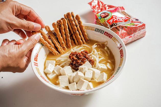 (3)のせる! 温めた木綿豆腐とビスケットの「アスパラガス」を盛りつけ、白髪ネギと肉味噌をのせれば完成。アスパラガスは丼の縁にのせると浸水を防げるため、食感の変化を楽しみやすい