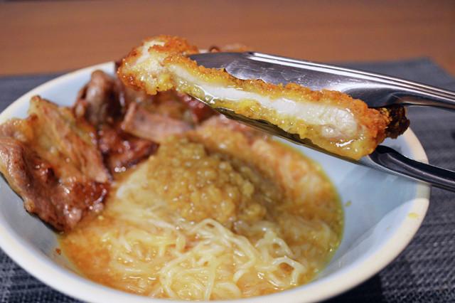 (4)搾る! 仕上げはファミチキを半分に切ったらトングなどを使ってファミチキを搾り、肉汁を垂らしたら完成。3種のアブラマシマシのスタミナ満点ガッツリとうふ麺を堪能せよ!