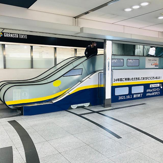 東京駅にて、高低差が少ないエスカレーターの形を生かしたE4系引退の記念ラッピング。運行開始当初の黄色帯のセレクトもうれしい
