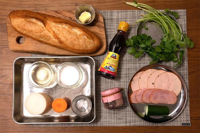 左上から時計まわりに、フランスパン、バター、ヌックマム、パクチー、ハム、チャーシュー、キュウリ、レバーペースト。(トレー内・なます用)酢、砂糖、塩、人参、大根