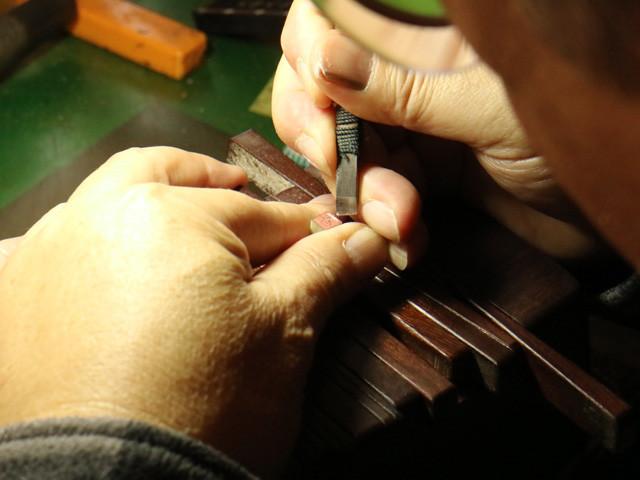 ハンコ作りの作業風景。6㎜角のロウ石に鏡文字で字入れ(筆で書き込み)し、その筆跡に沿って彫っていく。印刀は自分で研いだものを何種類も使い分ける